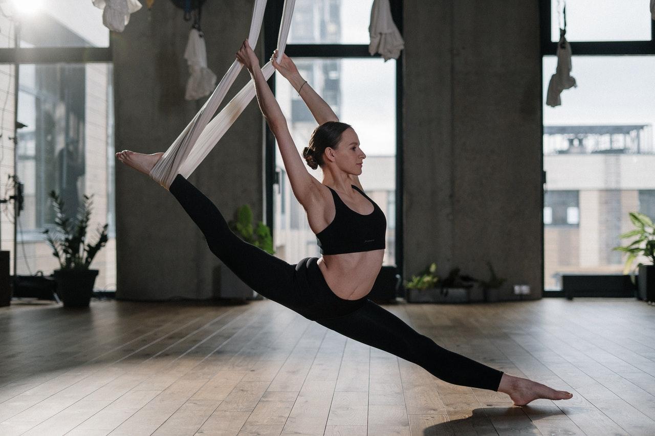 Frau trainiert am Vertikaltuch